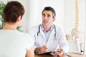Médecin de sexe masculin écrire quelque chose vers le bas tandis que le patient parle — Photo