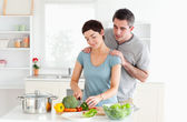 Man massaging his wife while she is cutting vegetables — Stock Photo