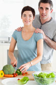 Husband massaging his wife while she's cutting vegetables — Stock Photo