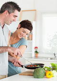 Gorgeous Woman looking into a pan her husband is holding — Stock Photo