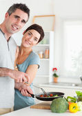 Gorgeous Woman and her pan-holding husband looking into the came — Stock Photo