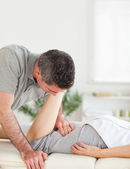 A chiropractor stretches woman's leg — Stock Photo