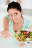Cute young woman offering salad — Stock Photo