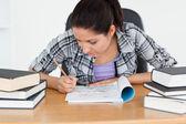 Ung student skriver in i sin skrivbok — Stockfoto