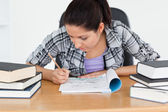 Young student writing into her exercise book — Stock Photo