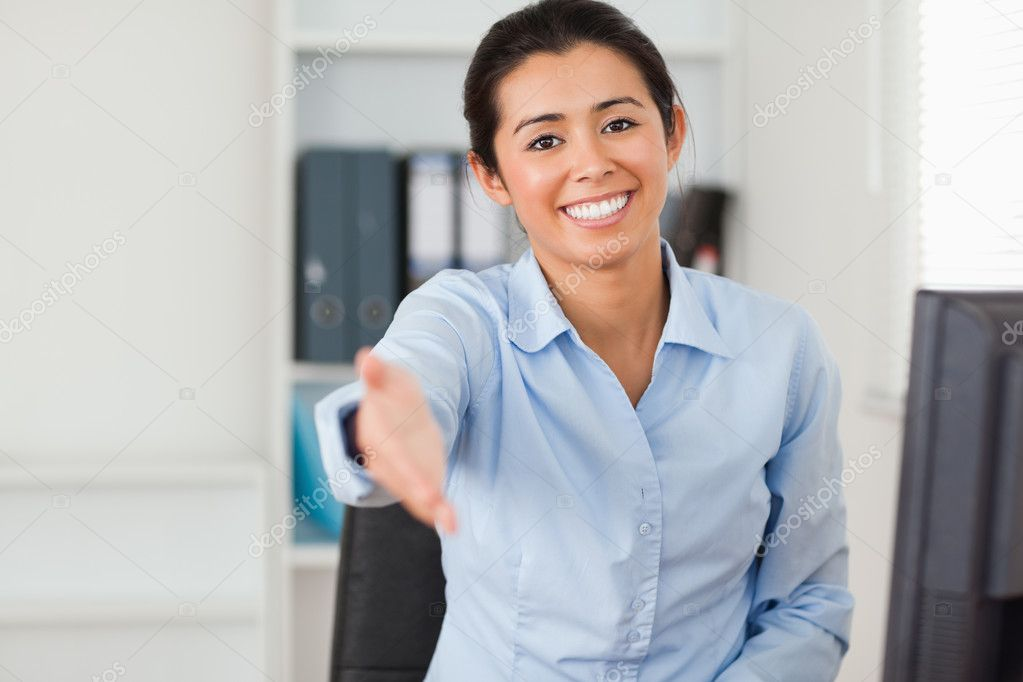 Good looking woman inviting somebody to seat while looking at the camera at the office — Stock Photo #11180733