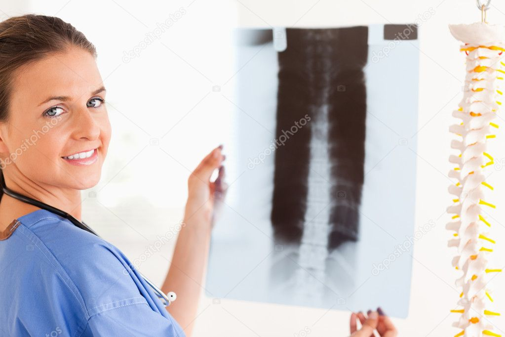 Brunette smiling doctor with a stethoscope and a x-ray in the surgery — Stock Photo #11181332