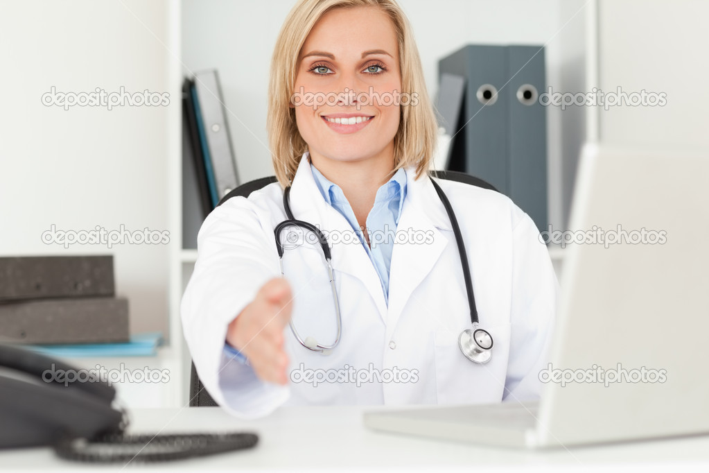 Blonde smiling doctor giving hand in her office — Stock Photo #11182049
