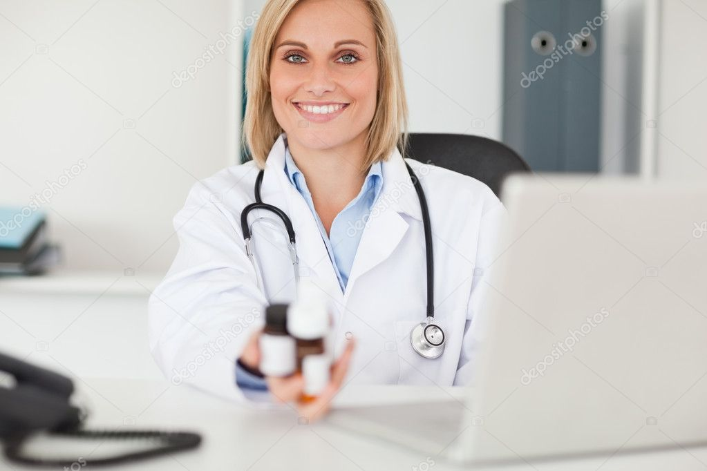 Smiling doctor holding medicine in her office  Stock Photo #11182051