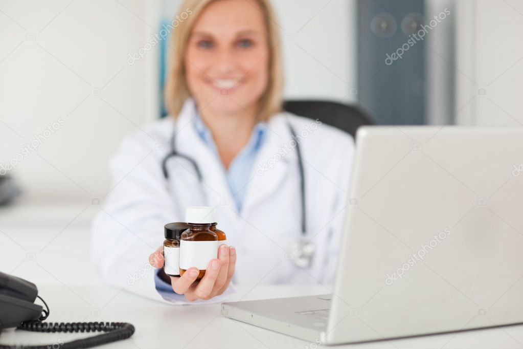Smiling blonde doctor presenting medicine in her office — Stock Photo #11182054