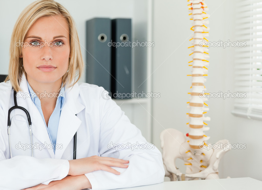 Serious blonde doctor with model spine next to her looks into camera in her office — Stock Photo #11182100