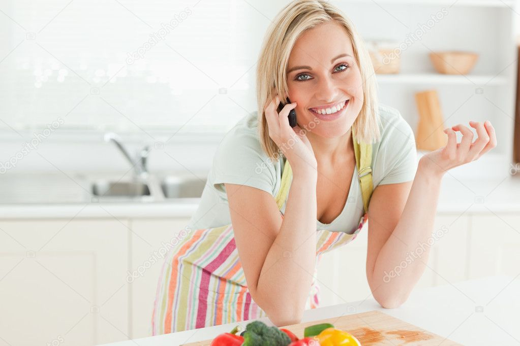Close up of a gorgeous woman on phone looking into camera in the kitchen  Stock Photo #11182161