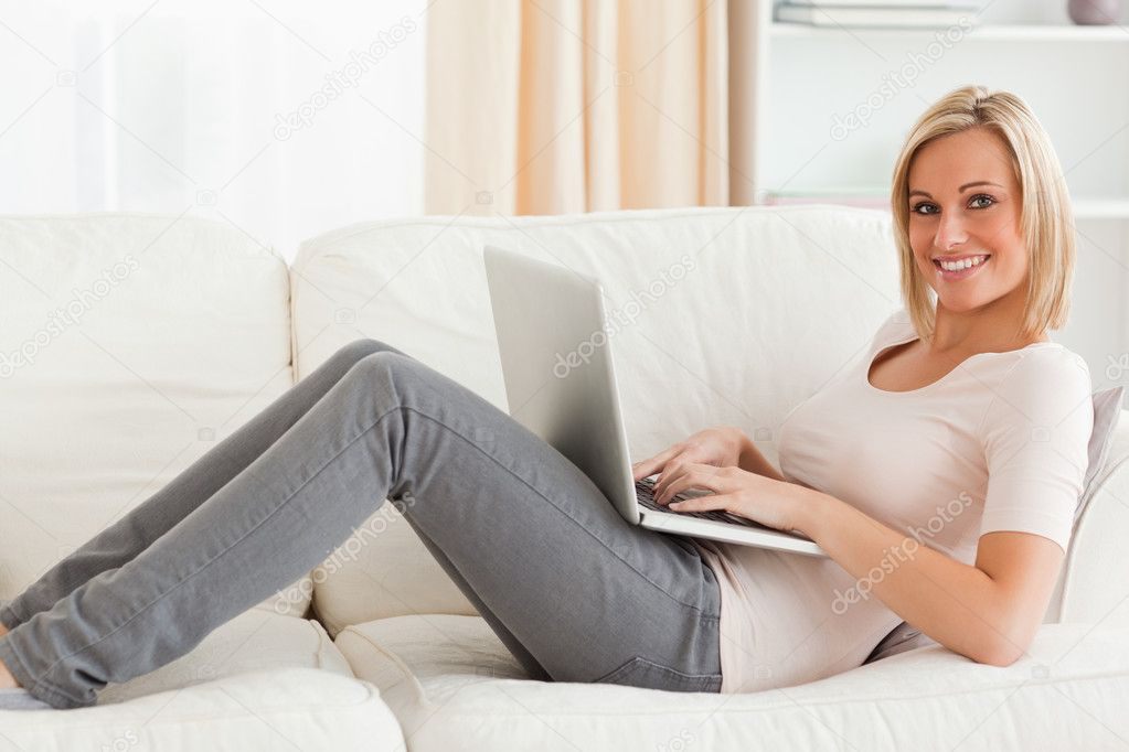 Smiling woman with a laptop lying on a sofa in her living room — Stock Photo #11183233