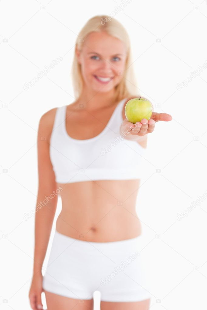Glorious young woman holding an apple in a studio  Stock Photo #11184759