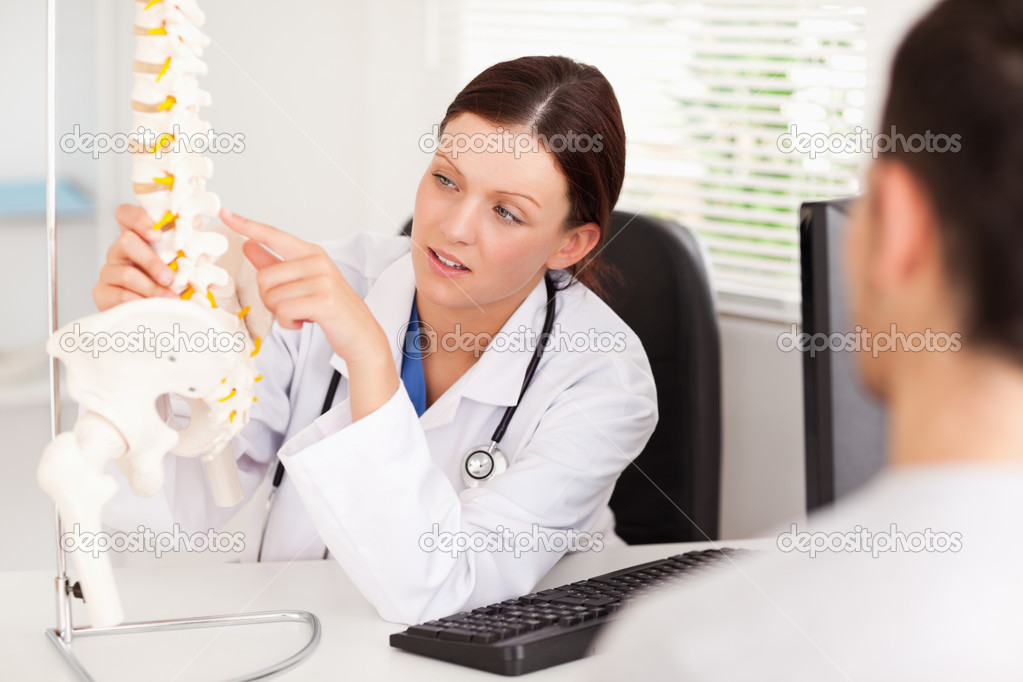 A female doctor is pointing on a bone in a spine — Stock Photo #11185051