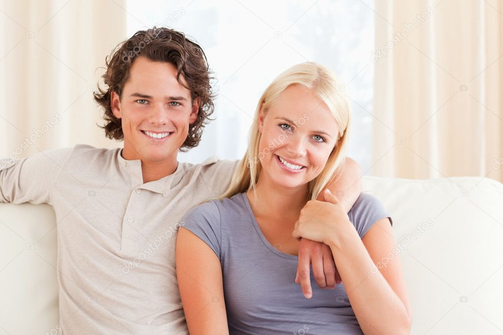 Couple sitting on a sofa while looking at the camera — Stock Photo #11185569
