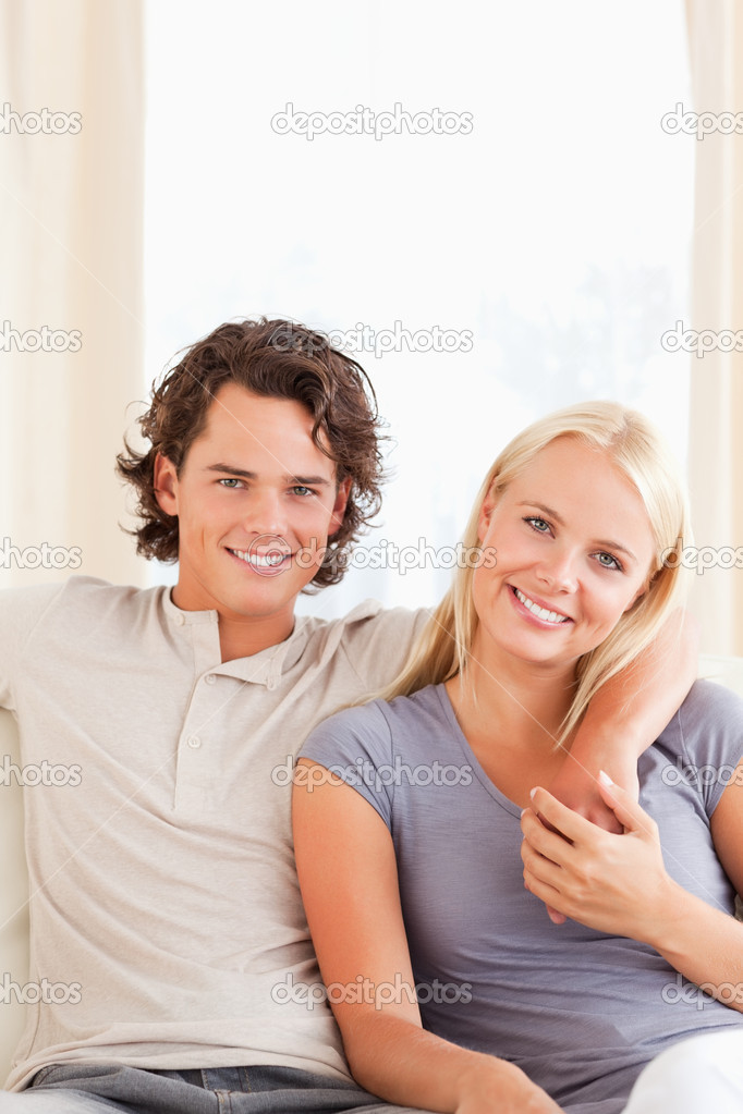 Portrait of a couple sitting on a sofa while looking at the camera — Stock Photo #11185570