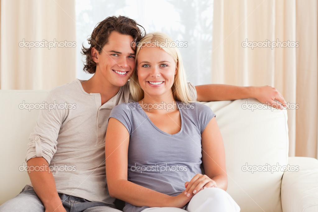 Smiling couple sitting on a sofa while looking at the camera — Stock Photo #11185593