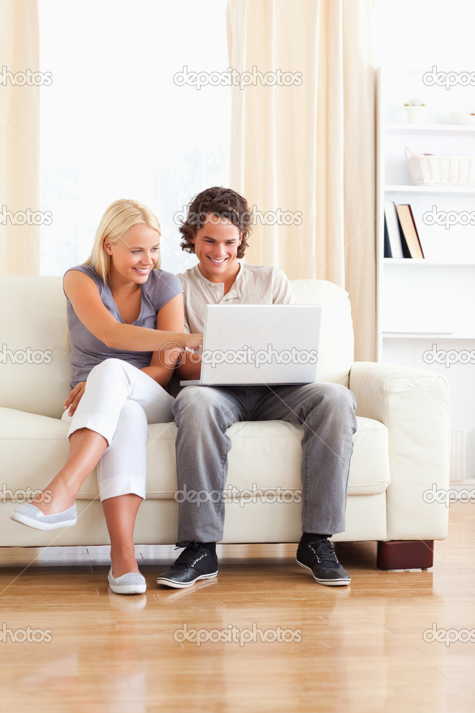 Portrait of a smiling in love couple using a laptop in their living room — Stock Photo #11185783