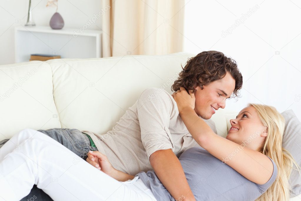 Cute couple hugging while lying on a sofa   Photo by Wavebreakmedia. Cute couple hugging   Stock Photo   Wavebreakmedia  11186248