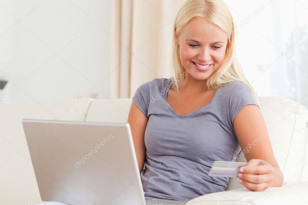 Woman looking at her credit card while holding her laptop in her living room — Stock Photo #11186390