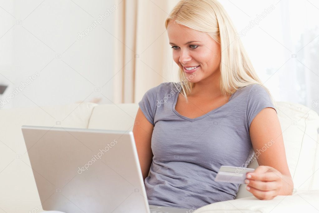 Woman looking at her laptop while holding  her credit card in her living room — Stock Photo #11186409