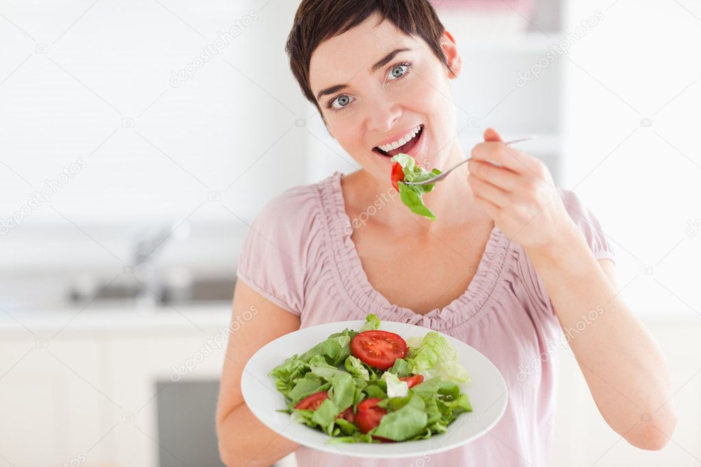 Good-looking woman eating salad in the kitchen — Stock Photo #11186943