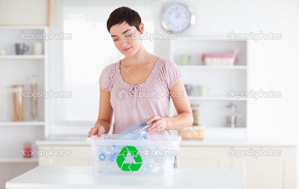 Charming Woman putting bottles in a recycling box in a kitchen — Stock Photo #11187257