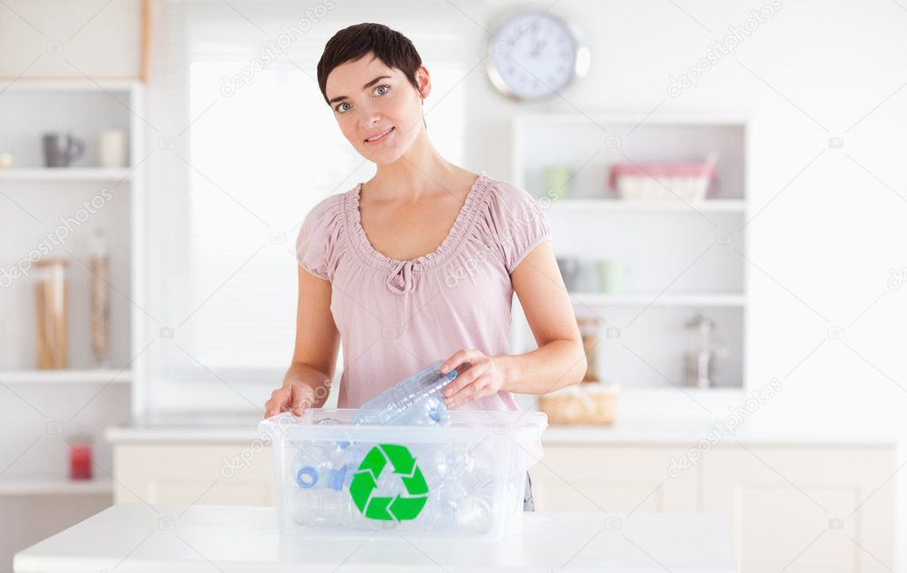 Smiling Woman putting bottles in a recycling box in a kitchen — Stock Photo #11187258