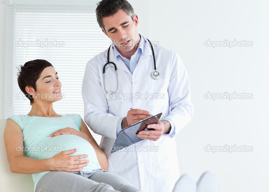 Pregnant woman lying down talking to her doctor in a room — Stock Photo #11189201