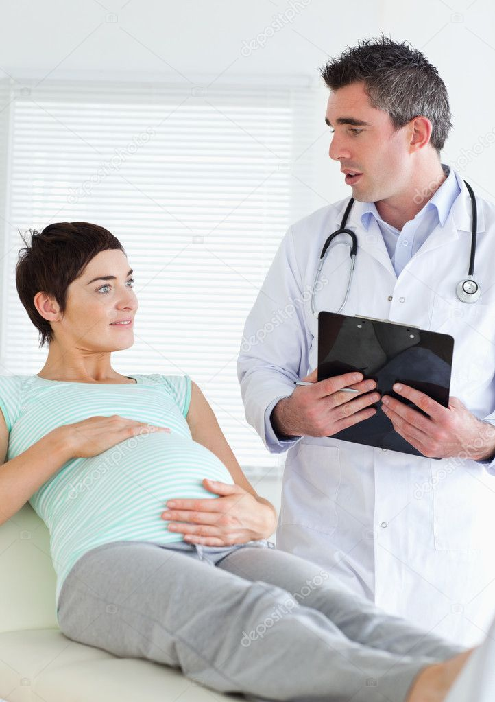 Doctor talking to a pregnant woman in a room — Stock Photo #11189204