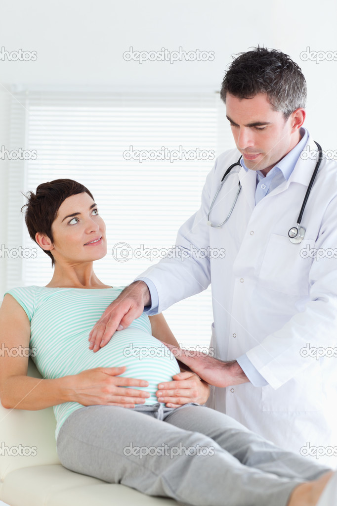 Doctor examining a pregnant woman's tummy in a room — Stock Photo #11189215