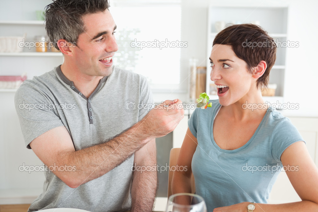 Man feeding his cute wife in a dining room — Stock Photo #11189413