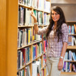 Portrait of a student choosing a book — Stock Photo