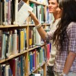 Portrait of young students choosing a book — Stock Photo