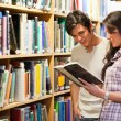 Young adults reading a book — Stockfoto