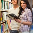 Portrait of young students holding a book — Stockfoto