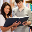 Portrait of happy students reading a book — Stock Photo