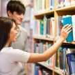 Students choosing a book on a shelf — Stock Photo