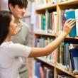 Portrait of students choosing a book on a shelf — Stock Photo