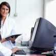 Smiling female scientist posing with a monitor — Stock Photo