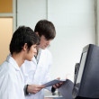 Portrait of male scientists using a monitor — Stock Photo