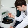 Young chemist using a centrifuge - Stock Photo