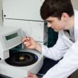 Young chemist using centrifuge — Stock Photo #11191107