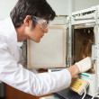 Male scientist using a laboratory chamber furnace - Stock Photo