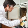 Stock Photo: Male scientist using laboratory chamber furnace