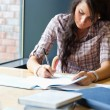 Portrait of beautiful student writing essay — Stockfoto #11191364