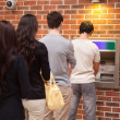 Young queuing to withdraw cash — Stock Photo