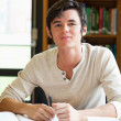 Smiling male student writing an essay — Stock Photo