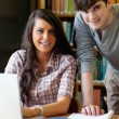 Portrait of young students working together with a laptop — Stock Photo